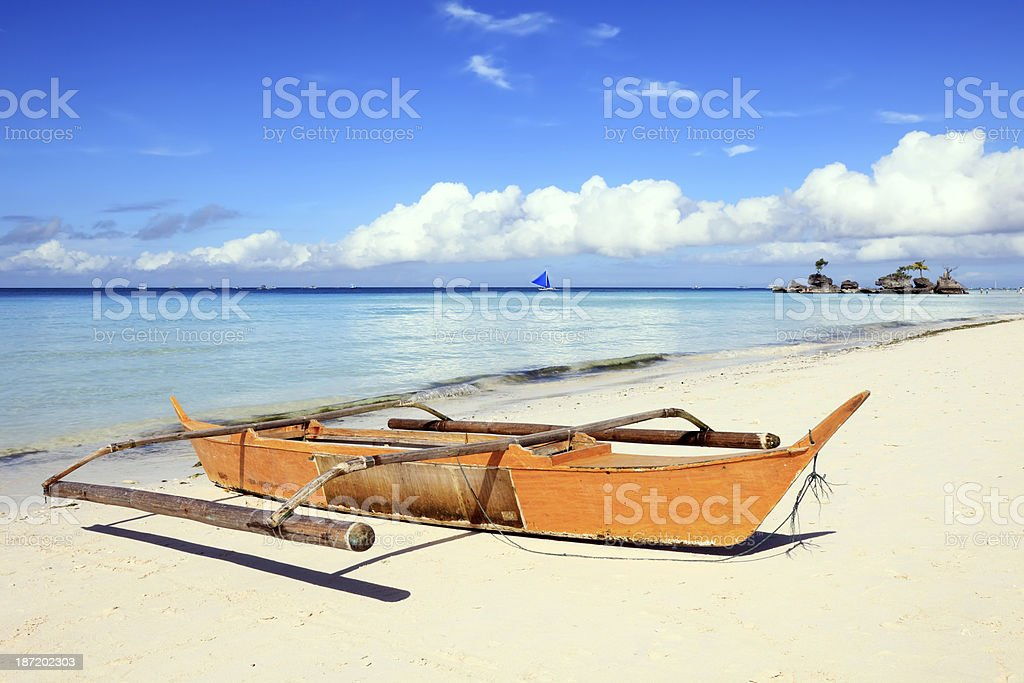 Outrigger boat stranded on white sandy beach royalty-free stock photo