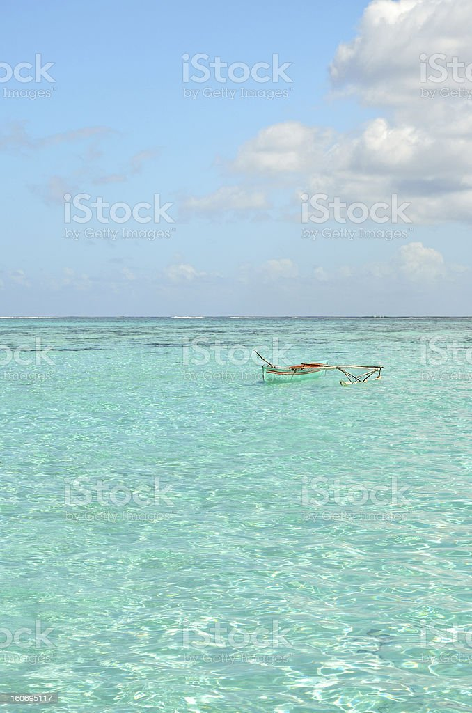 Outrigger canoe in clear lagoon water royalty-free stock photo