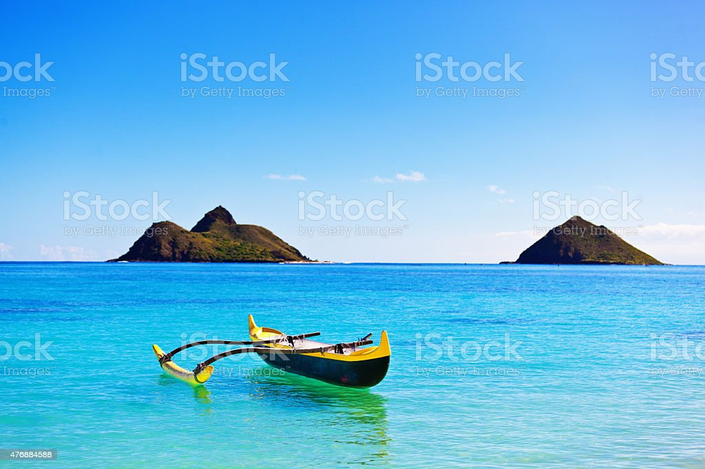 Outrigger Canoe off Lanikai Beach with Pacific Islands, Oahu, Hawaii stock photo