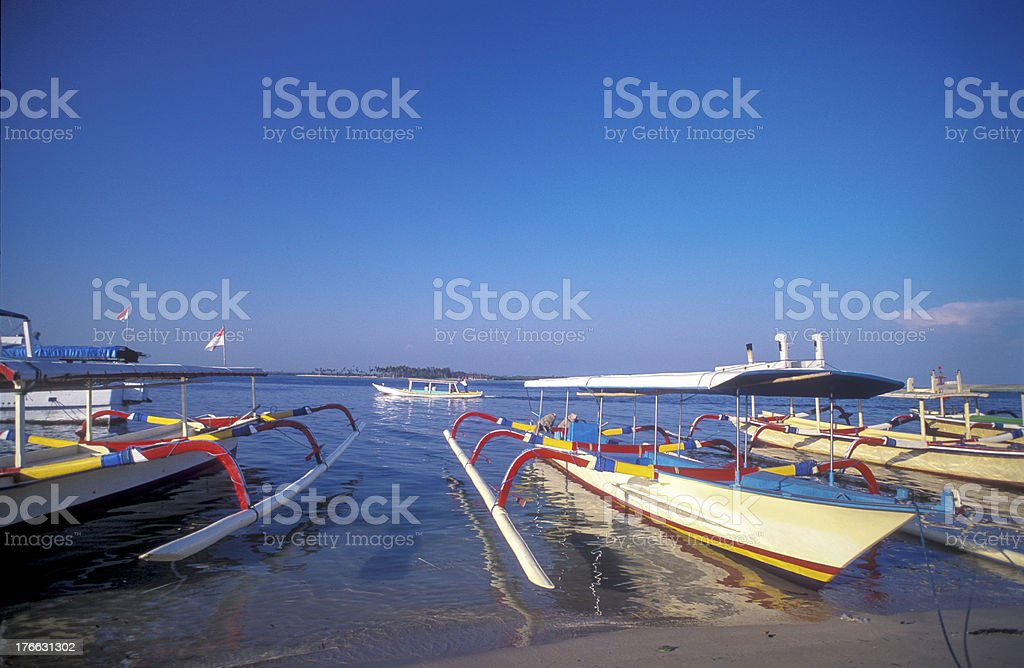 Outriggers, Bali, Indonesia. Sandy beach, blue sky. royalty-free stock photo
