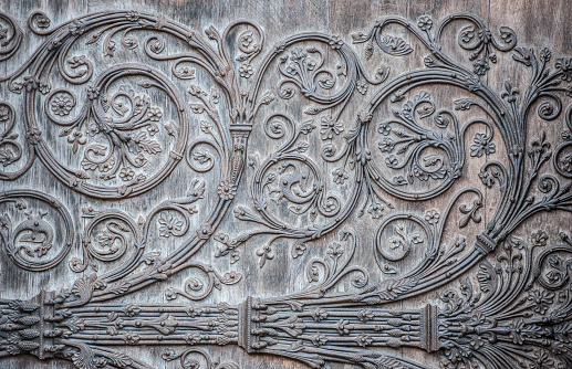 Ornament twirly metal fittings on ancient medieval door. The portal with the doors was constructed between 1210-1220, and the cathedral was restored 1845. The original creator of the artwork is unknown and the copyright long expired. Notre Dame, Paris, France.