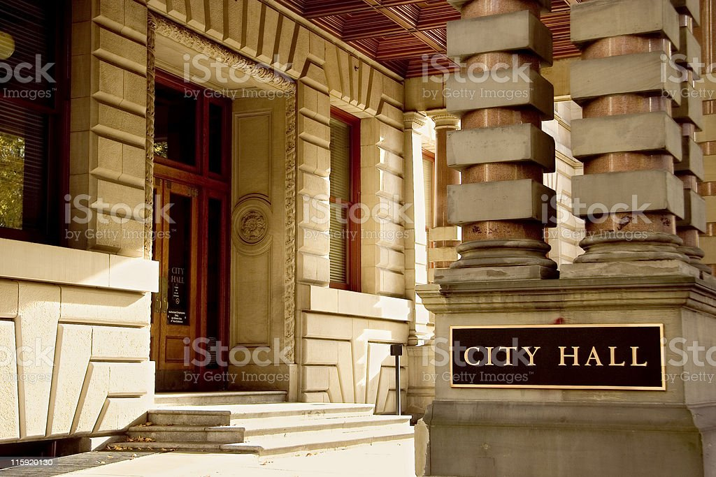 Outside of a city hall with a black plate on two columns stock photo