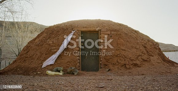Outside of a Hogan (Navajo Hut) with a Large Rock Formation Behind It