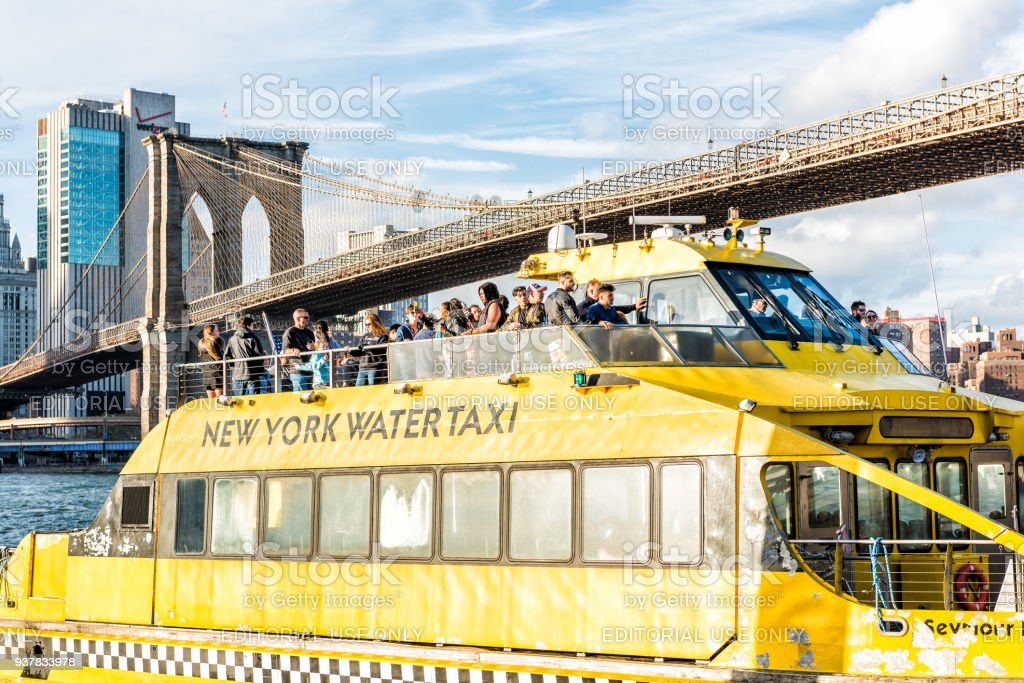 Outside outdoors in NYC New York City Brooklyn Bridge Park with many crowd of people on water taxi yellow ferry cruise tour boat stock photo