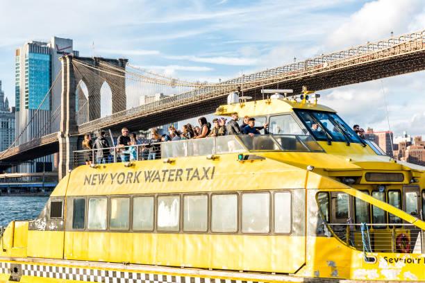 buiten buiten in nyc new york brooklyn bridge stadspark met veel menigte van mensen op water taxi gele veerboot cruise tour boot - rondvaartboot stockfoto's en -beelden