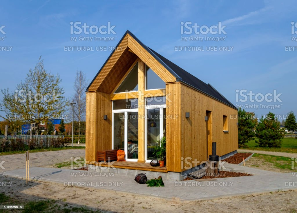 Outside view of a tiny house made of wood, against a blue sky