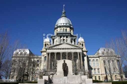 Illinois State Capitol Building with Abraham Lincoln statue and a clear blue sky.
