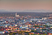Aerial view of modern European city outskirts in evening light with  densely built industrial, commercial and residential buildings, power plant with chimneys and Bavarian Alps in background, Maxvorstadt Sendling Munchen Bayern Germany