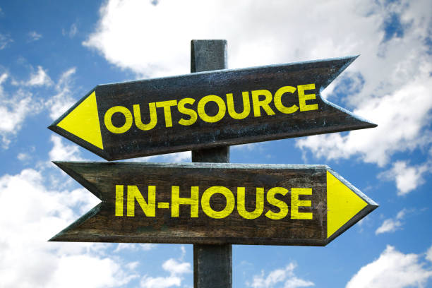 Outsource / In-House sign Outsource / In-House signpost with sky background outsourcing stock pictures, royalty-free photos & images