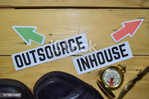 Outsource or Inhouse opposite direction signs with boots,eyeglasses and compass on wooden vintage background. Business, education and finance concepts