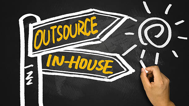 outsource or in-house signpost hand drawing on blackboard outsource or in-house signpost concept hand drawing on blackboard outsourcing stock pictures, royalty-free photos & images
