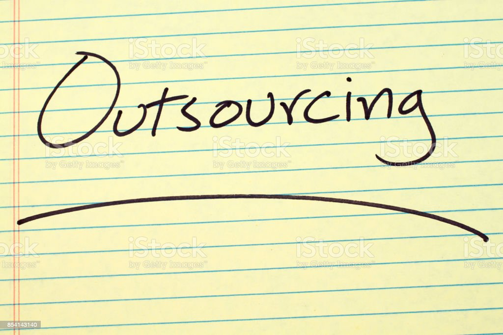 Outsourcing On A Yellow Legal Pad stock photo