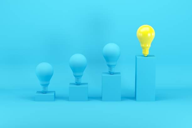 Herausragende helle Glühbirne unter blauen Glühbirnen auf Balkendiagramm auf blauem Hintergrund. Minimales Ideenkonzept. – Foto