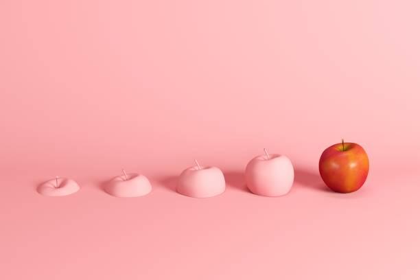 Herausragender frischer roter Apfel und Apfelscheiben in rosa auf rosa Hintergrund gemalt. Minimales Fruchtgedankkonzept. – Foto