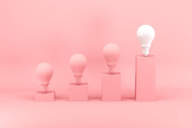 Hervorragende weiße Glühbirne unter rosa Glühbirnen auf Balkendiagramm auf rosa Hintergrund. Minimales Ideenkonzept. – Foto