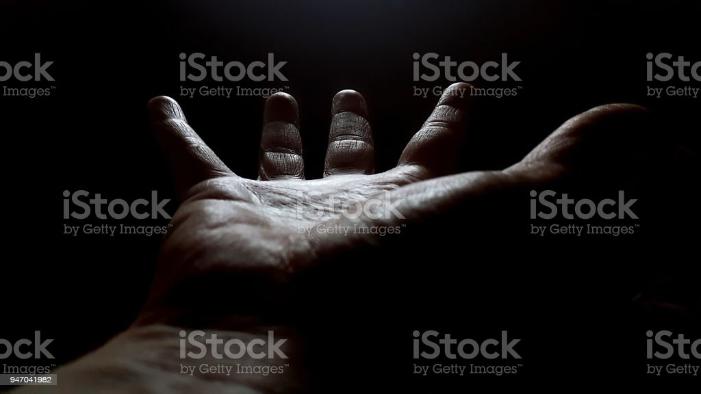 Outstretched Hand on a Black Background stock photo