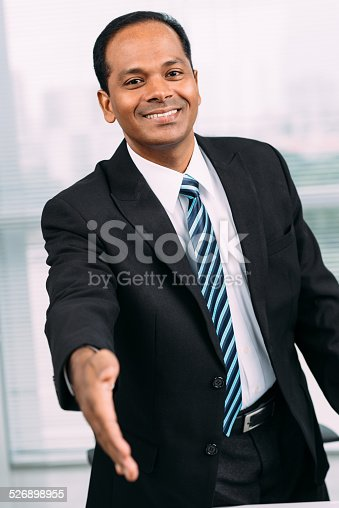 Smiling Indian businessman outstretching hand for a handshake