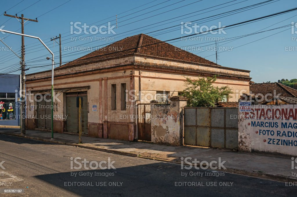 Outworn old house and wall with painted placard in empty street on the sunset at São Manuel. stock photo