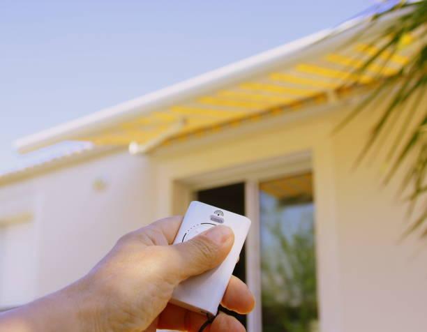 ouverture du storre banne main qui utilise une télécommande électrique pour ouvrir un store banne extérieur sur la terrasse awning stock pictures, royalty-free photos & images