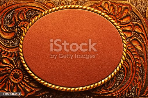 An oval shaped belt buckle resting on top of a tooled leather surface.