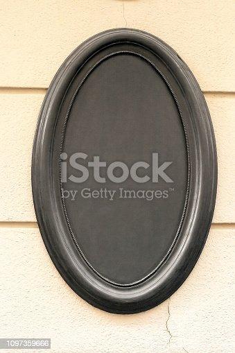istock Oval empty blank black signboard on wall 1097359666