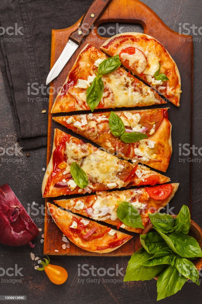 Oval homemade pizza with feta cheese, tomatoes and basil on a wooden board. stock photo
