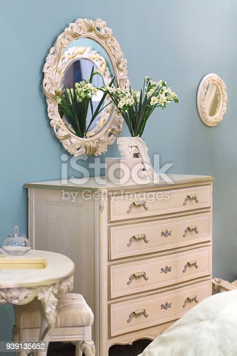 1136239089 istock photo Oval mirror in beautiful retro style, chest of drawers in girl bedroom. 939135652