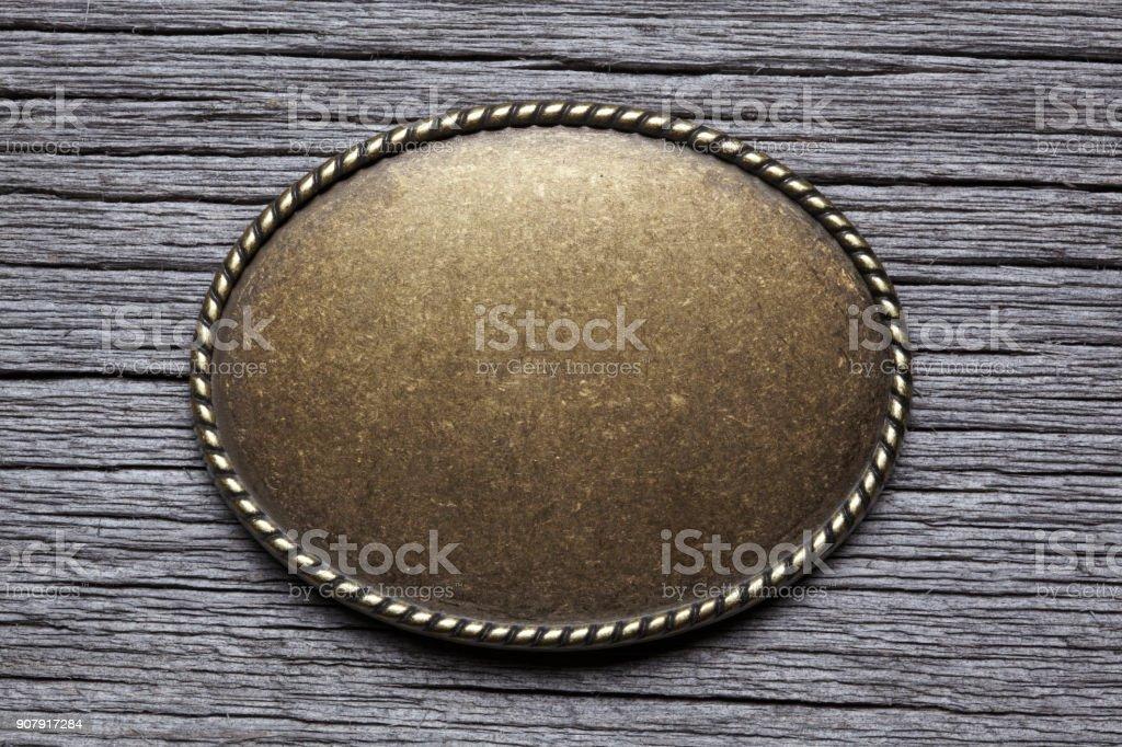 Hebilla plata oval sobre superficies de madera resistida foto de stock libre de derechos