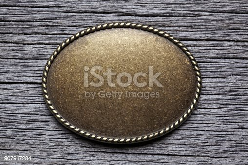 An oval shaped belt buckle resting on top of a gray weathered wood surface.