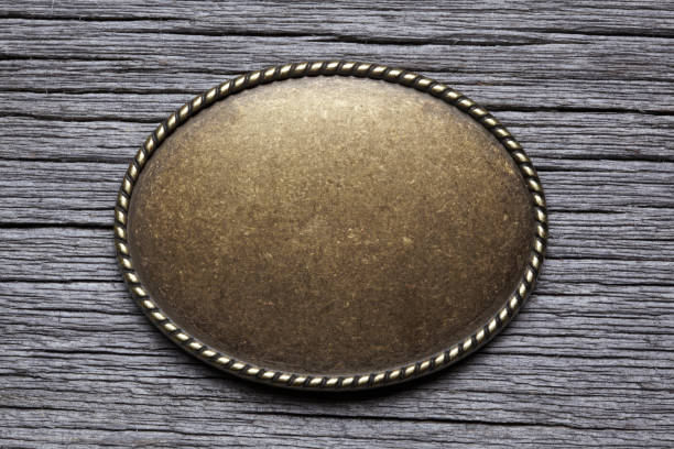 oval silver buckle on weathered wood surface - belt stock photos and pictures