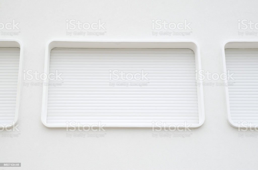 Oval windows with new white external blinds on wall stock photo