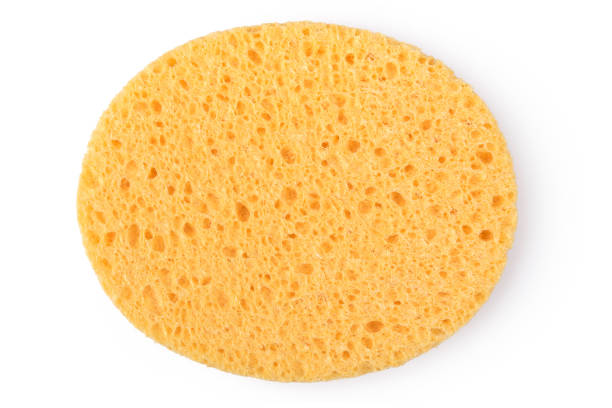 oval yellow sponge cleansing puff for face or cleaning surface texture isolated on white background on top view - spugna per le pulizie foto e immagini stock