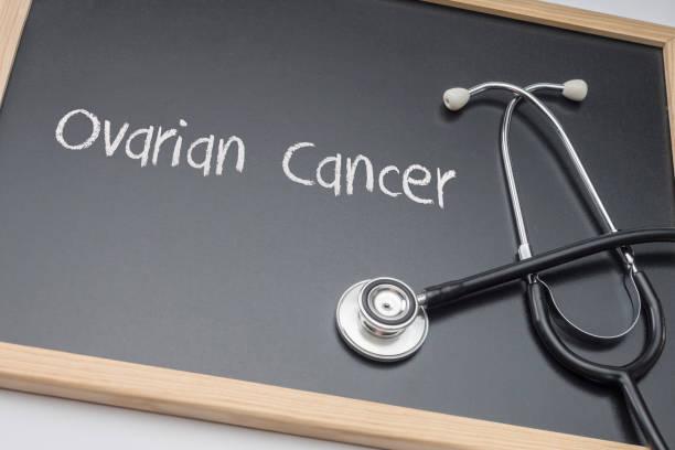 cáncer de ovario escrito en tiza sobre un pizarrón negro al lado de un estetoscopio, imagen conceptual - ovarian cancer ribbon fotografías e imágenes de stock
