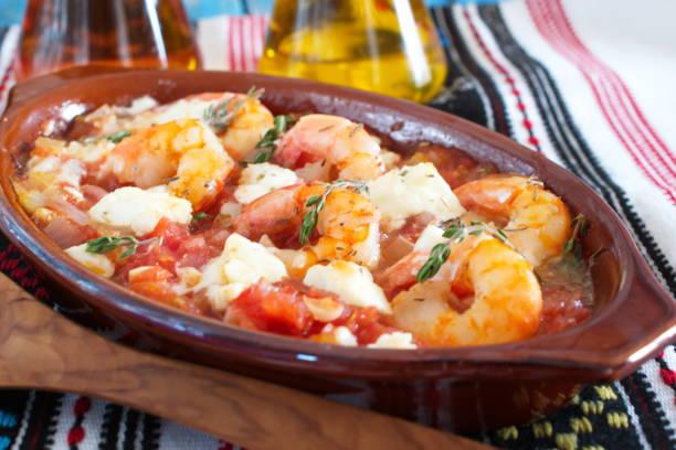 ofen gesichert garnelen mit feta, tomaten, paprika, thymian in einer traditionellen keramischen form auf einem abstrakten hintergrund. gesunde ernährung-konzept. mediterranen lebensstil - ofengemüse mit feta stock-fotos und bilder