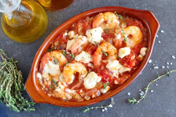 ofen gesichert garnelen mit feta, tomaten, paprika, thymian in einer traditionellen keramischen form auf einem abstrakten hintergrund. gesunde ernährung-konzept. mediterranes lebensgefühl. - ofengemüse mit feta stock-fotos und bilder