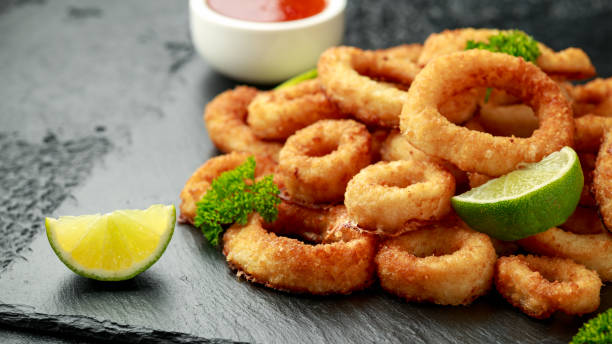 Oven baked breaded calamari rings served with lime wedges, sweet chilli sauce and mayonnaise stock photo