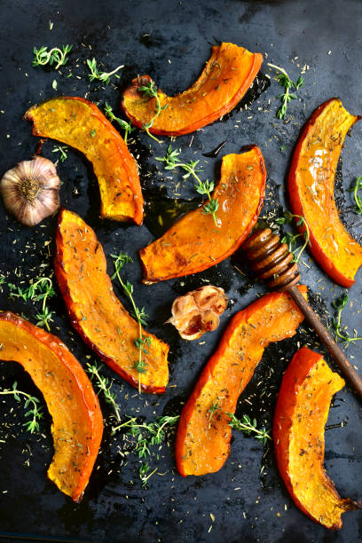Oven baked pumpkin slices Oven baked pumpkin slices with garlic and thyme served with honey on a black metal tray.Top view. squash vegetable stock pictures, royalty-free photos & images