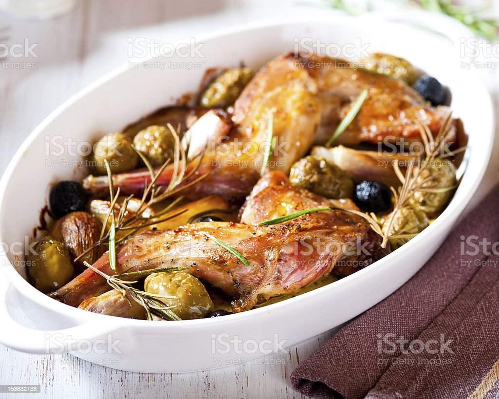 Oven baked rabbit legs with olives and rosemary stock photo