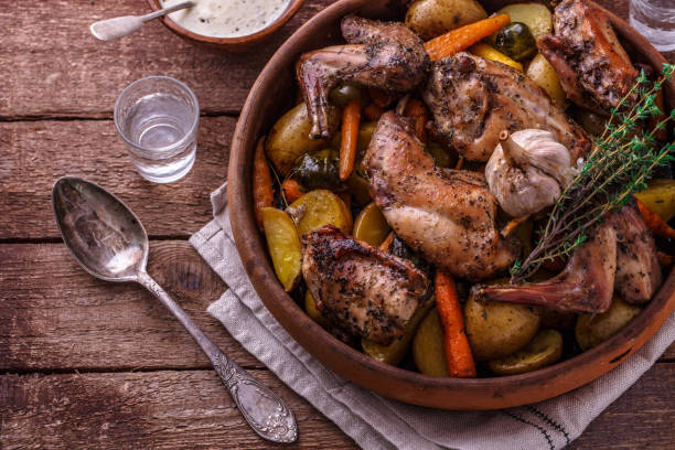 Oven baked rabbit with root vegetables and herbs, rustic style stock photo