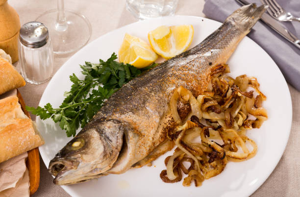 Oven baked sea bass fish stock photo