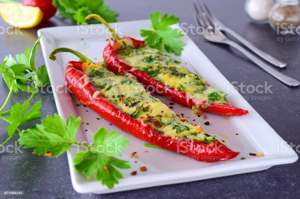 Oven cooked red paprika stuffed with cheese, garlic and herbs on a white plate with parcley and cherry tomatoes an abstract grey background. healthy eating concept. Mediterranean. Selective focus - foto de acervo
