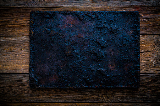 Oven roast tray in black aged on rustic vintage wooden background