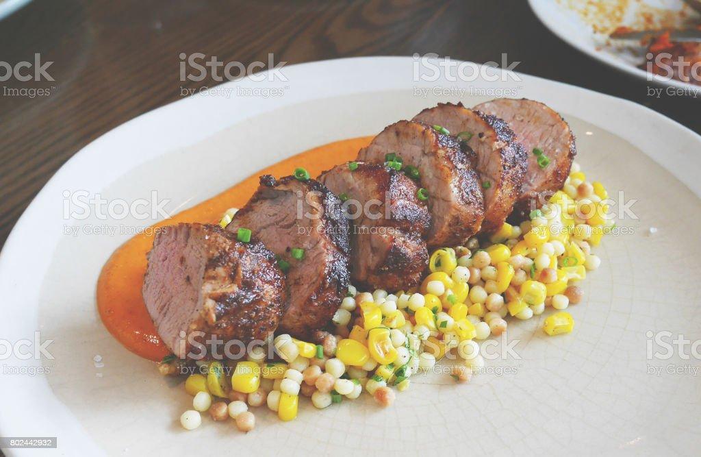 Oven roasted pork tenderloin with romesco and fregola corn salad stock photo