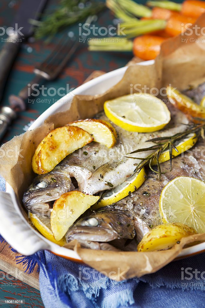 Oven roasted trout and roasted vegetables on a rustic table royalty-free stock photo