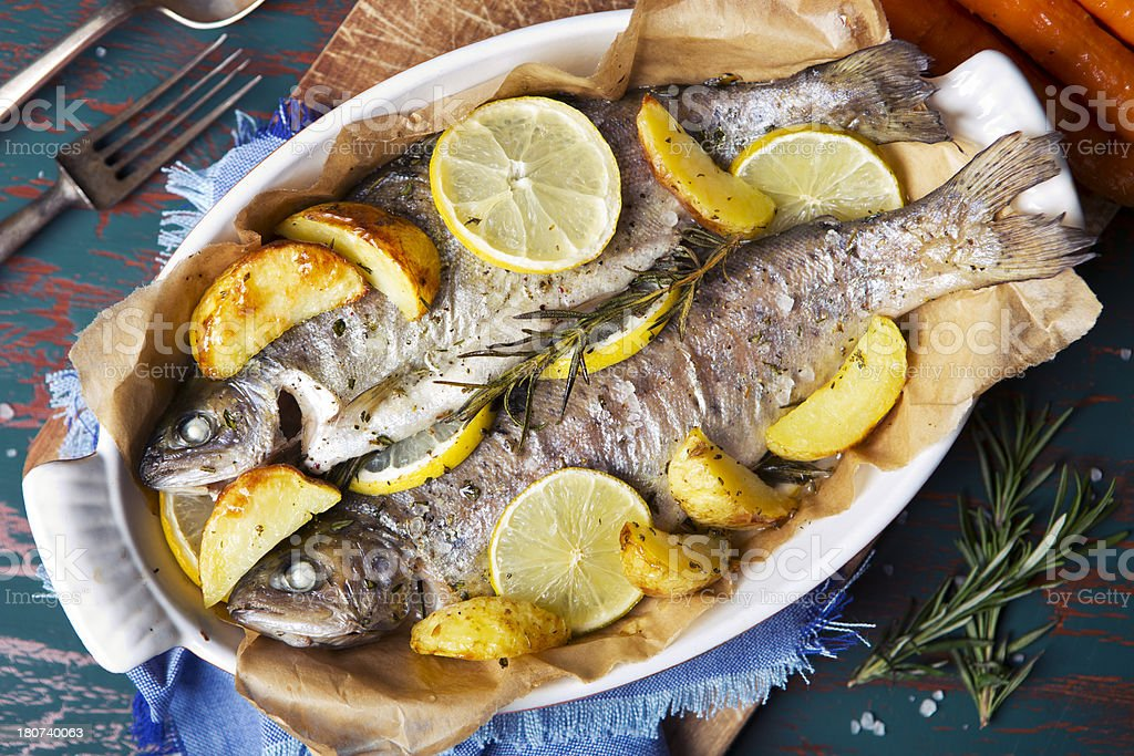 Oven roasted trout in a casserole on a rustic table royalty-free stock photo