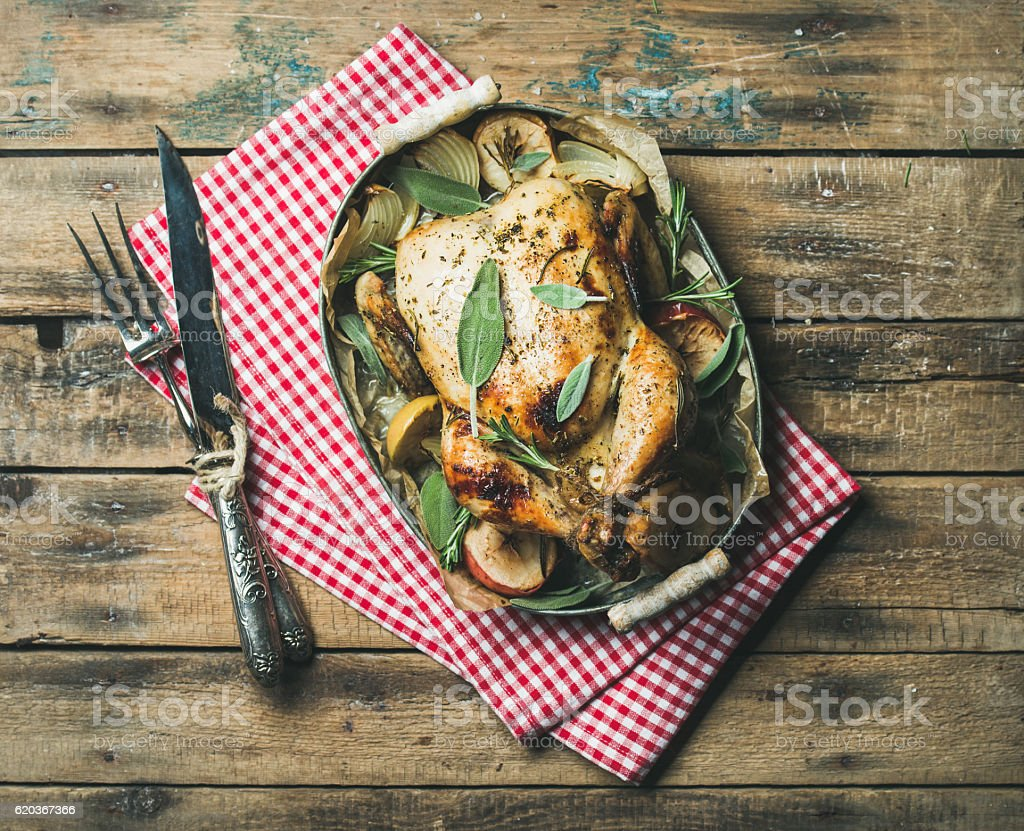Oven roasted whole chicken in tray over wooden background zbiór zdjęć royalty-free