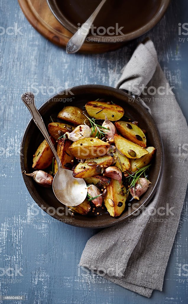 Oven-baked potatoes with pumpkin seeds, garlic and herbs (autumn style) stock photo