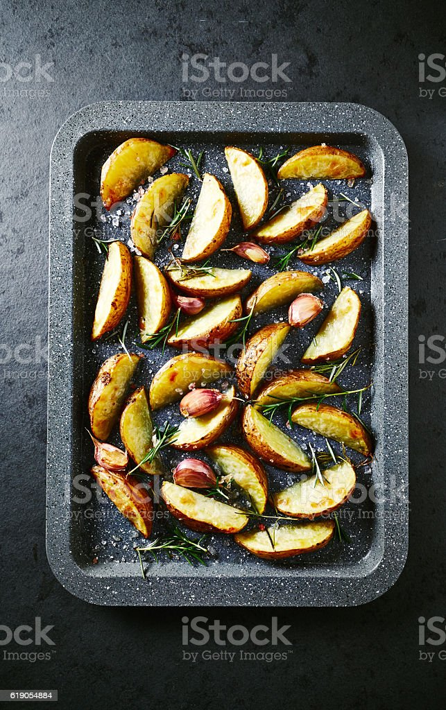 Oven-roasted potatoes with rosemary and garlic stock photo