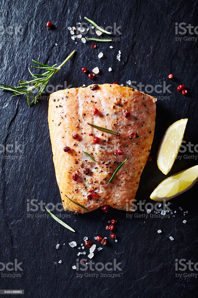 Oven-roasted salmon fillet on a black slate stock photo