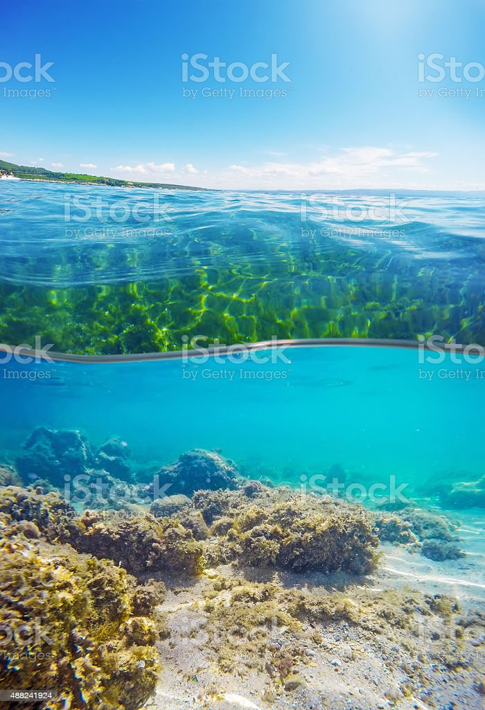 over and under water surface of a Sardinian beach stock photo